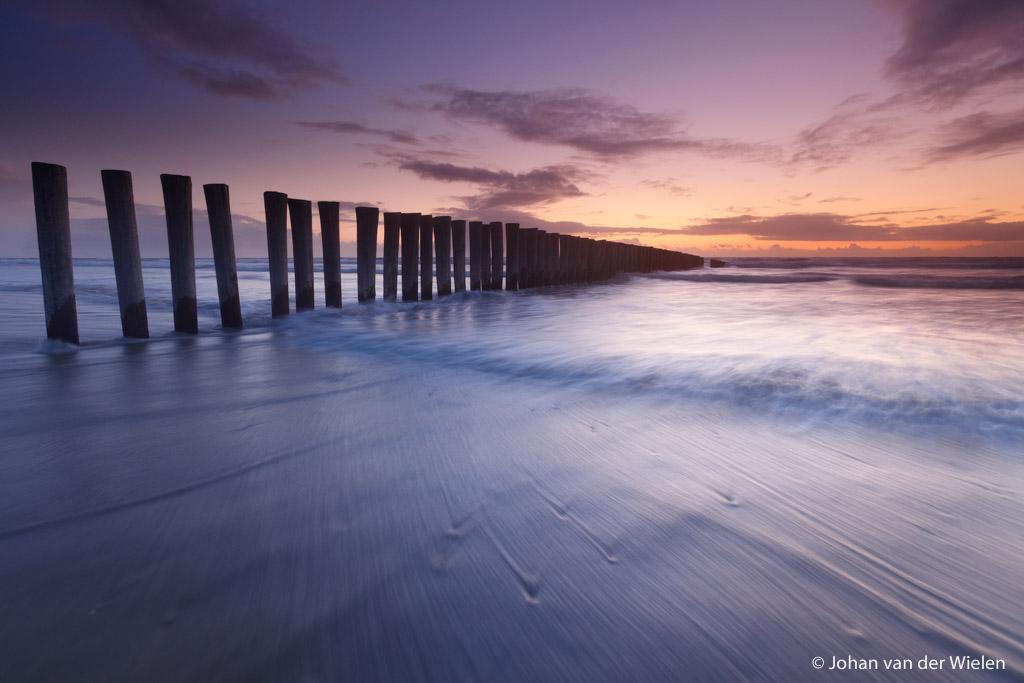 palen in de noordzee bij zonsondergang