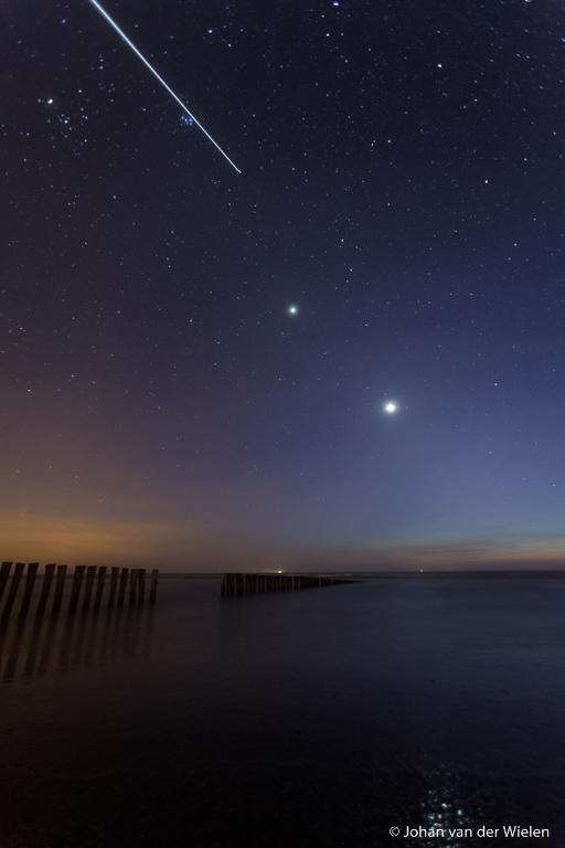 houten golfbreker bij heldere sterrenhemel, het ISS komt voorbij