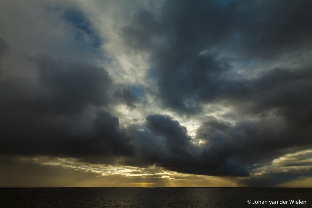 de zon priemt door het dikke wolkendek en laat zonnestralen op de waddenzee vallen