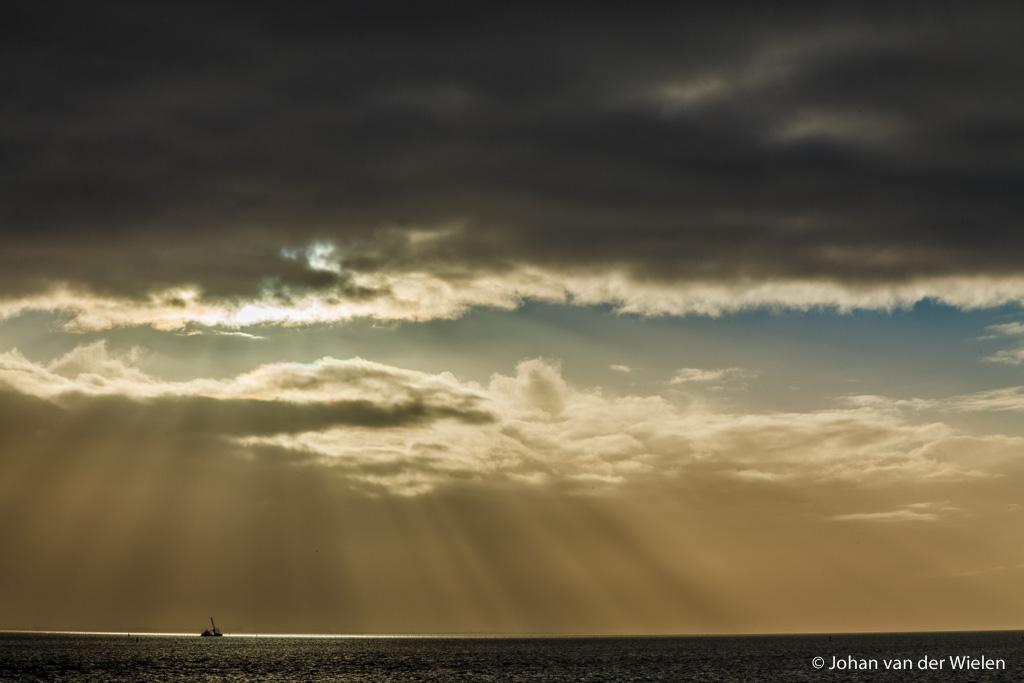 de zon priemt door een gat in het donkere wolkendek en verlicht precies een baggerschip in de waddenzee