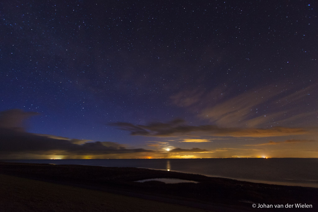 ondergaande maan bij helder sterrenhemel boven de waddenzee, in de verte het licht van de wal