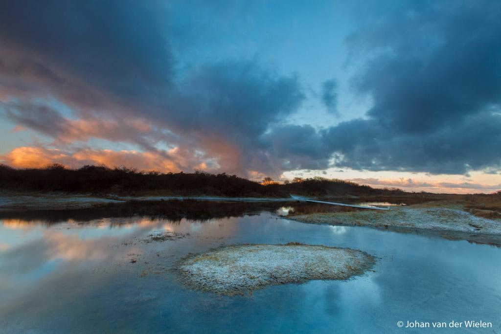 de opkomende zon verlicht de wolken met warme kleuren, reflectie van de wolken in de poelen van de kwelders