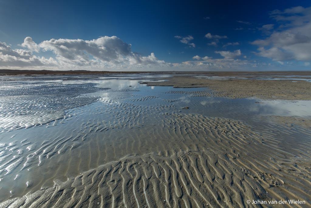 wolken reflecteren in het natte zand van het noordzeestrand