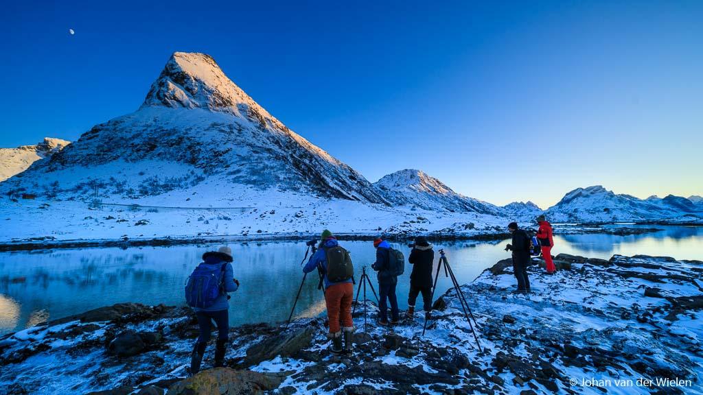 De arctisch aandoende landschap reflecteert in het stilstaande water van het fjord.