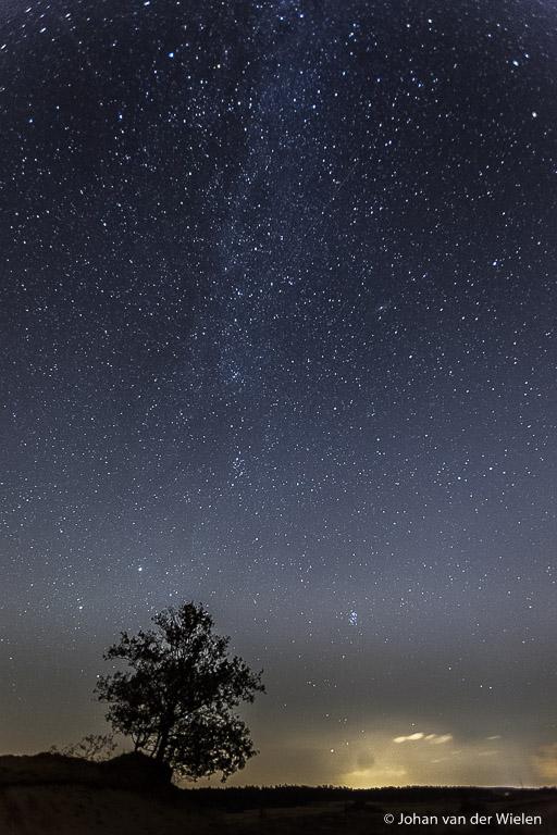 De melkweg is moeilijk te zien, maar hier zichtbaar vanaf het Kootwijkerzand met in de verte lichtvervuiling van de stad Apeldoorn.