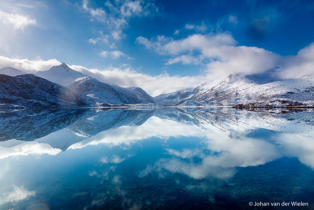 De perfecte weerspiegeling van blauwe lucht en witte bergen creëren een oneindige wereld. Lofoten, Noorwegen.