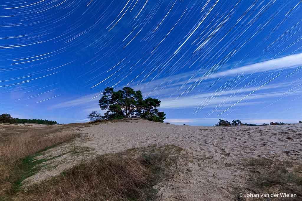 Sterrensporen: tijdens de nacht draait de aarde en trekken de sterren sporen langs de hemel. De voorgrond wordt weer verlicht door een volle maan
