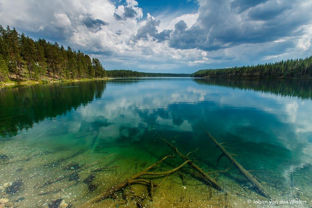 Dubbel effect: de wolken contrasteren extra tegen de blauwe lucht en in de voorgrond kun je de boomstammen onder water zien