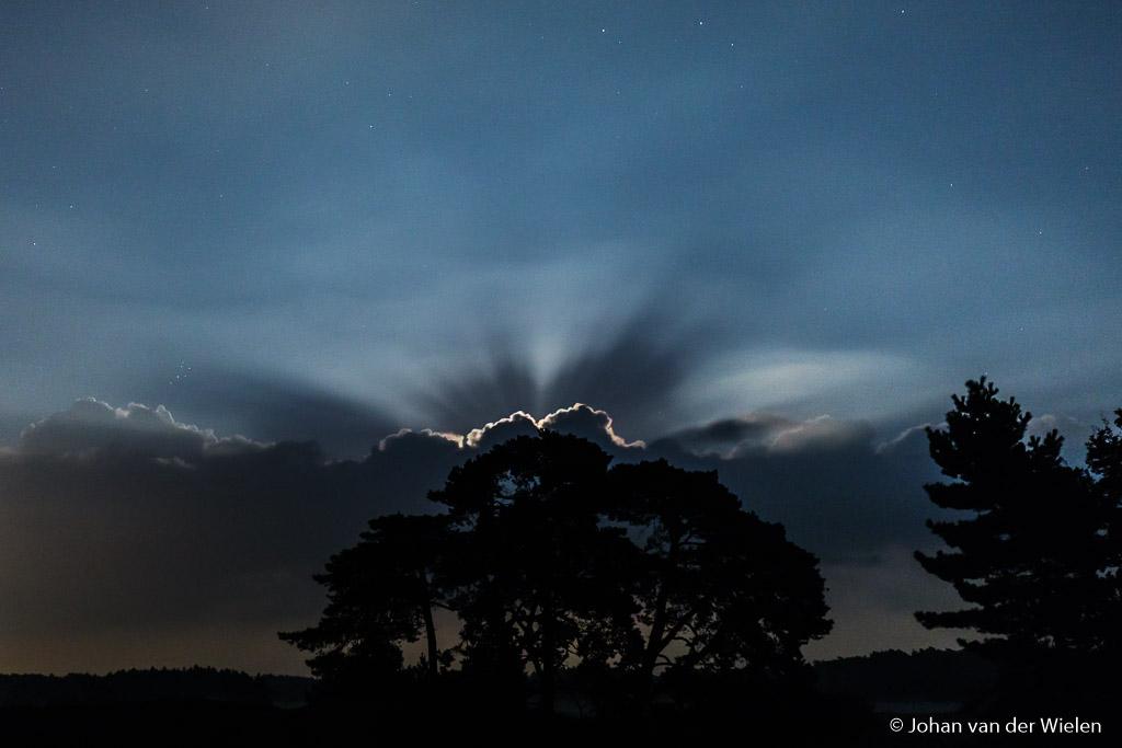 De volle maan straalt achter de laatste wolk
