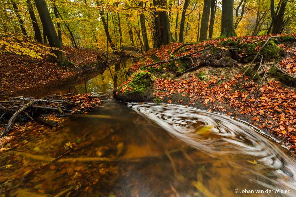 Zelfde beeld maar nu met 2,5 sec. belichting (bij lage ISO en hoger diafragmagetal), het schuim heeft bewogen tijdens de foto en zorgt voor een ronddraaiende beweging, het water is mooi vlak en laat de kleuren door.