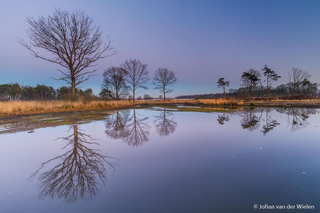 Na de zonsondergang richt ik mijn blik naar achteren. In het verstilde water van het ven reflecteren alle bomen als in een spiegel. Op de achtergrond is de rode band van de aardschaduw zichtbaar