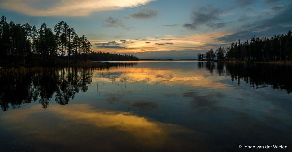 Een serene zonsondergang in Finland, reflectie van aangelichte wolken in het rustig kabbelende water. ISO100, f/16 en 1/8 sec.