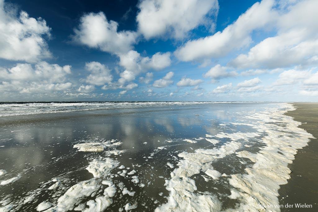 Hollandse wolkenlucht, reflecterend in het natte noordzeezand.