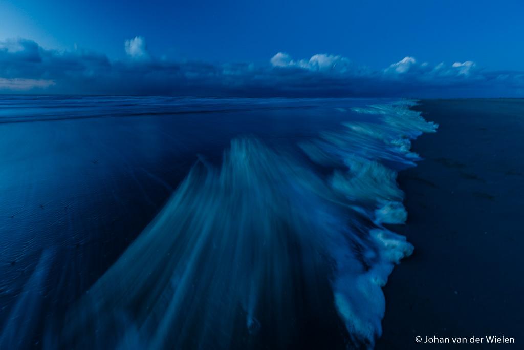 Blauwe uurtje, intens blauwe kleur. Door sterke wind wordt schuim af en aan geblazen op het strand