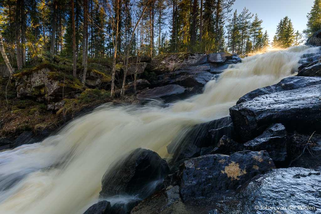 Het licht van de zon beschijnt nog net even de bovenkant van de waterval