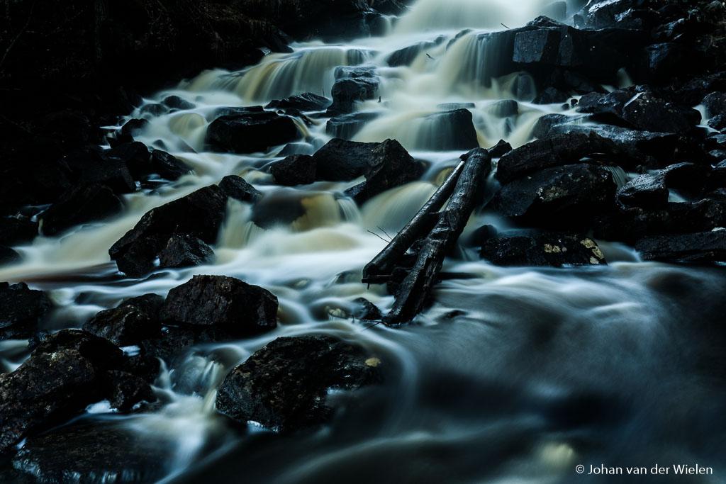 Onderaan de waterval is het donker en zwart
