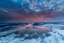 Zonsondergang boven het besneeuwde wad