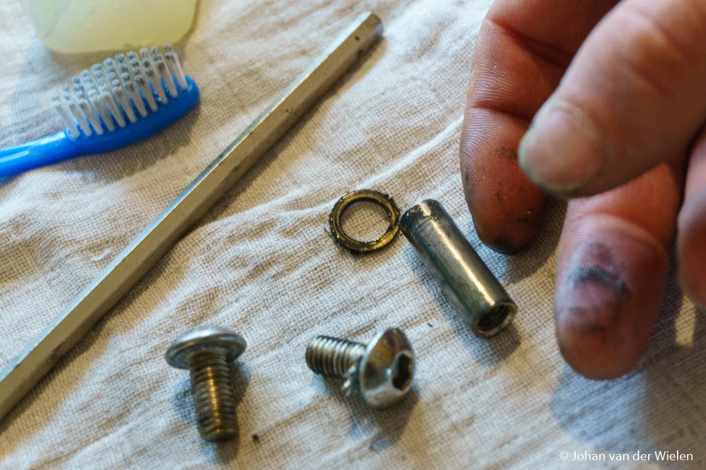De scharnieren bestaan uit een busje, koperen ringen en een tweetal bouten. Mijn vingers laten duidelijk zien dat schoonmaken geen overbodige luxe is.