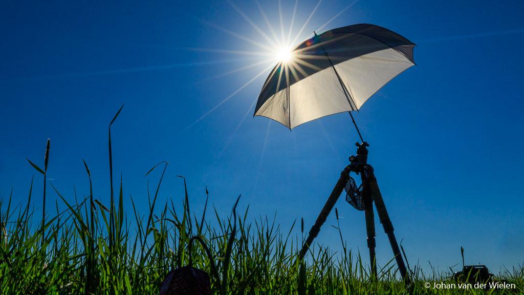 Witte paraplu in het veld geplaatst op een gewoon statief om de zon tegen te houden.