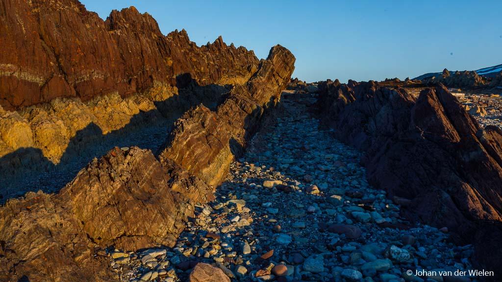 Imposante rotsformaties op Varanger in gouden nachtlicht. Maar waar zijn de kleuren?