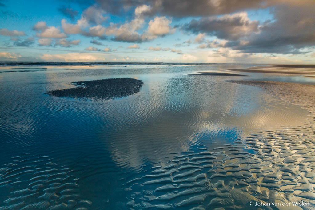 Reflectie in het water op het strand van Ameland. Door de sluitertijd van 1/30 zijn kleine rimpelingen nog steeds te zien.